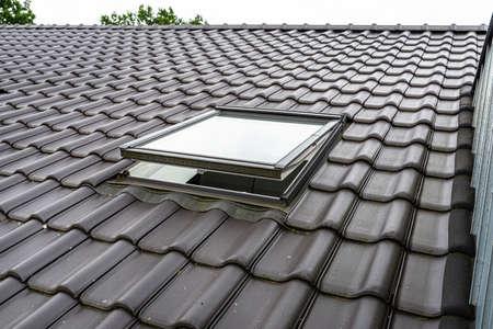 Photo pour One open roof window in the attic, visible anthracite ceramic tiles. - image libre de droit