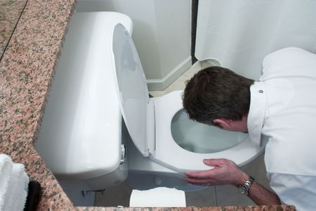 man kneeling by toilet bowl and throwing up