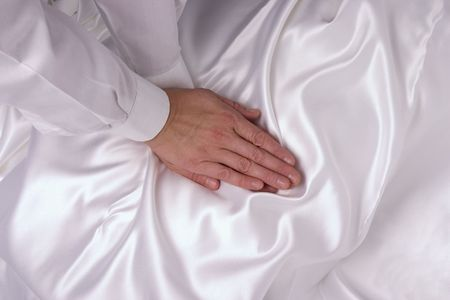 massaging hands with white sleeves on white silk