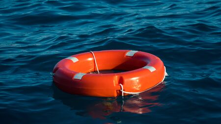Foto de Life buoy or rescue buoy floating on sea to rescue people from drowning man. Safety equipment. Light waves on a sunny day - Imagen libre de derechos