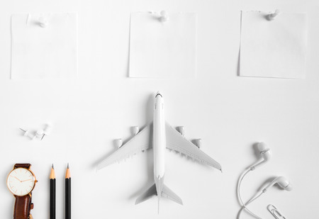Preparation for Traveling concept, watch, airplane, pencils, paper noted, earphone, push pin, on white background with copy space.