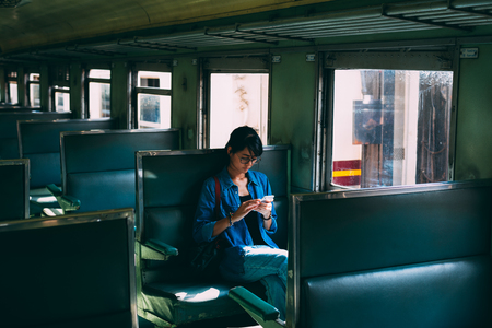 Foto de Asian woman traveler sits on train seat and used smart phone while wait train leaving station of the railway station - travel and transportation concept - Imagen libre de derechos