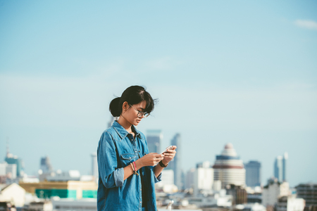 Photo pour Asian woman used smart phone reads and text message on her smart phone in the city scene background with copy space - image libre de droit