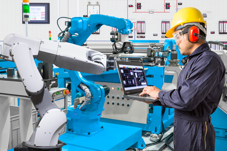 Photo pour Engineer using laptop computer for maintenance automatic robotic hand machine tool at industrial manufacture factory - image libre de droit
