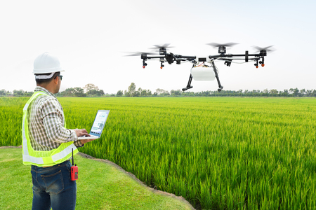 Foto per Technician farmer use wifi computer control agriculture drone fly to sprayed fertilizer on the rice fields, Smart farm 4.0 concept - Immagine Royalty Free