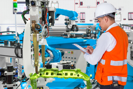 Photo pour Engineer checking maintenance daily of automated automotive robotic in production line of automotive industry - image libre de droit