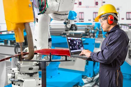 Photo pour Engineer using laptop computer maintenance robot grip automotive workpiece position, Smart factory concept - image libre de droit
