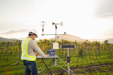 Photo pour Agronomist using tablet computer collect data with meteorological instrument to measure the wind speed, temperature and humidity and solar cell system in grape agricultural field, Smart farm concept - image libre de droit