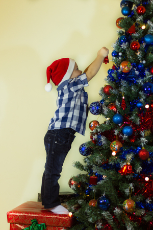 Little boy decorating the Christmas tree trying to reach as high as possible