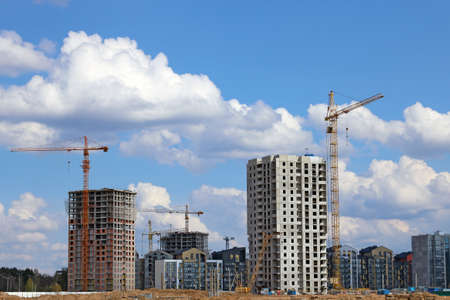 Photo pour View of tall cranes and houses under construction - image libre de droit