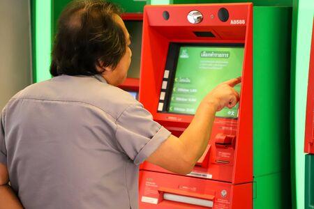 Photo pour Eelderly man uses an ATM. Thailand Bangkok March 2020 - image libre de droit