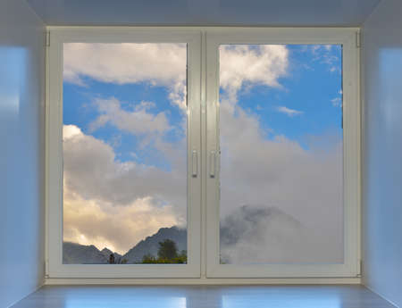 Photo pour Blue sky and mountain peaks in the clouds can be seen from the window. - image libre de droit
