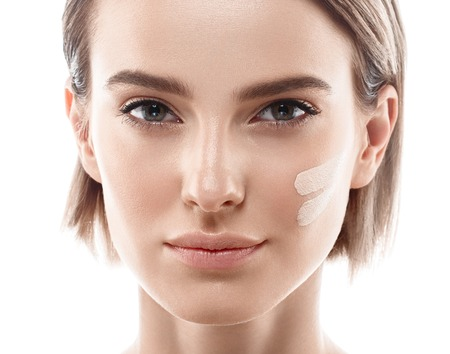Skin tone cream lines on woman face. Beautiful woman portrait beauty skin healthy and perfect makeup. Studio shot. Isolated on white.