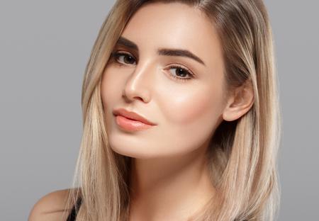 Foto de Beautiful young woman portrait smiling posing attractive blond with flying hair on gray background. Studio shot. - Imagen libre de derechos