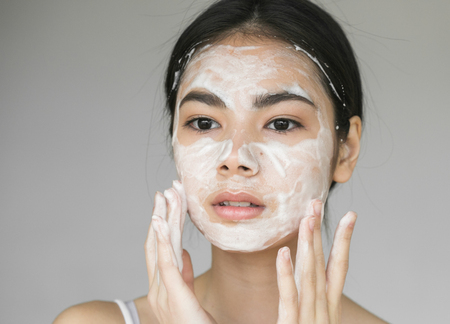 Photo pour Young beautiful woman washing her face with soap. Studio shot. - image libre de droit