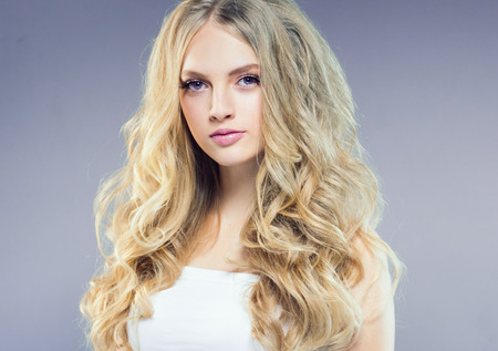 Foto de Beautiful blonde girl with long curly hair over purple background. Studio shot. - Imagen libre de derechos
