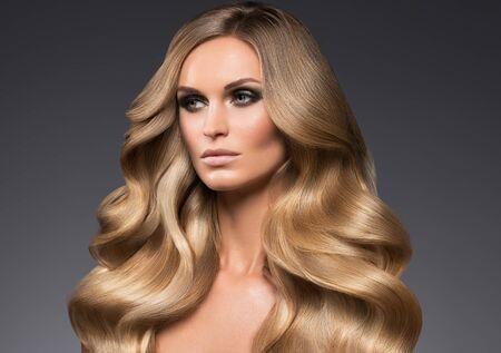 Photo pour Blond woman long hair curly natural fashion makeup. Studio shot. - image libre de droit