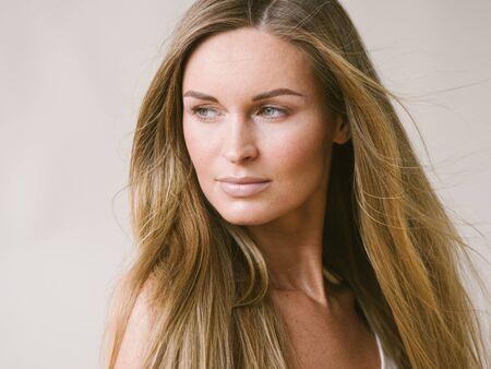 Photo pour Beautiful woman natural portrait girl with long blonde hair over white gray wall. Studio shot. - image libre de droit