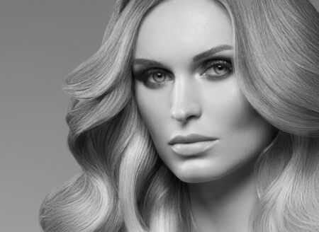 Photo for Healthy curly hair woman long blonde hairstyle female. Studio shot. Monochrome. Gray. Black and white. - Royalty Free Image