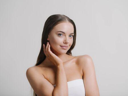 Photo pour Natural beauty woman with heands touching face long brunette hair beautiful neck and shoulders Studio shot. - image libre de droit