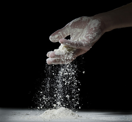 Wheat flour is poured from a man's palm.