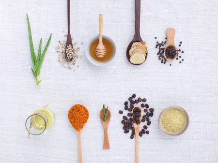 Foto de herb variety on rustic white background from top view, oil, coffee, beans, pepper, aloe vera, turmeric, ginger, rosemary - Imagen libre de derechos