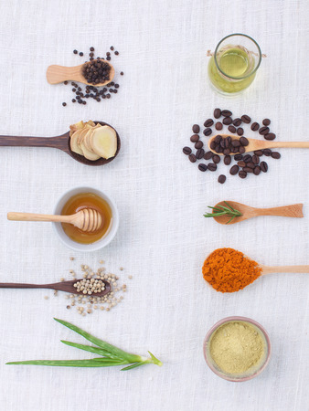 herb variety on rustic white background from top view, oil, coffee, beans, pepper, aloe vera, turmeric, ginger,