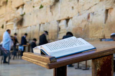 Western Wall also known as Wailing Wall in Jerusalem. The Bible Book in the foreground.