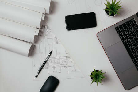 Photo pour Laptop, phone and rolls of drawings on the Desk in engineering. architectural background with rolls of technical drawings - image libre de droit