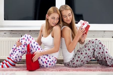 Two girls opening christmas gifts