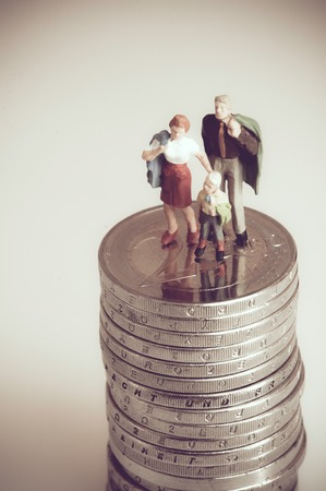 Miniature family on pile of coins.