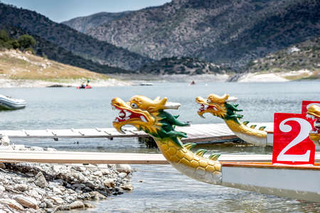 Photo pour Dragon boats moored at wooden pier or jetty on the lake - image libre de droit