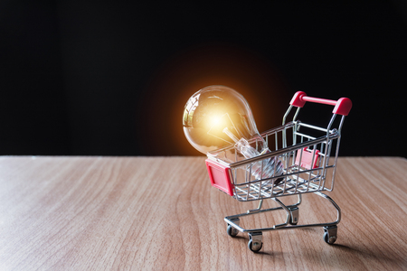 Energy saving light bulb with stacks of coins and shopping cart for saving, financial and shopping concept.