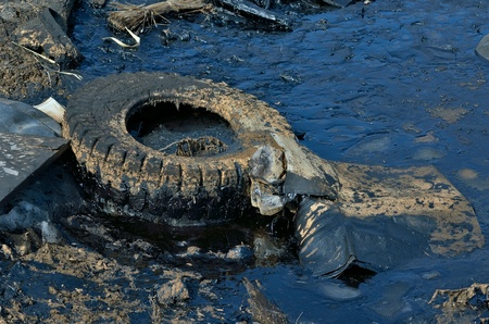 A rubbish heap with black oil pollution.