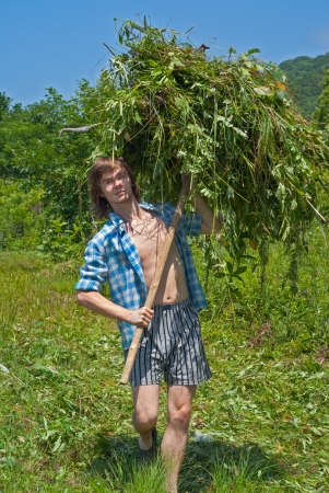 The young man is carrying a hay with hayfork on green meadow.の写真素材