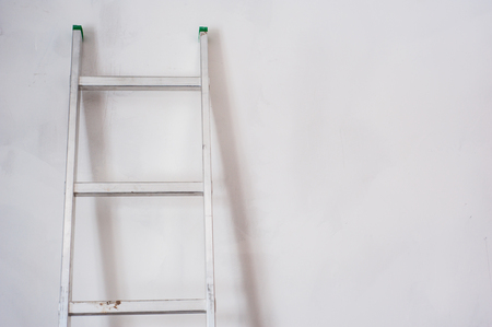 Aluminum ladder leaning against white wall. The concept of repair and construction