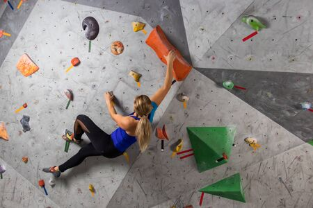 Photo pour Rock climber woman hanging on a bouldering climbing wall, inside on colored hooks. - image libre de droit