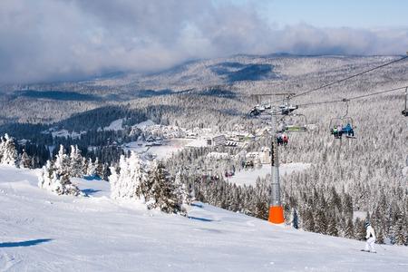 Kopaonik, Serbia - January 22, 2016: Ski resort Kopaonik, Serbia, ski slope, people on the ski lift, mountains, houses and buildings panorama