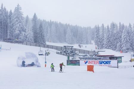 Kopaonik, Serbia - January 18, 2016: Panorama of ski resort Kopaonik during snowfall, people, skiers near ski lift, mountain view at winter time
