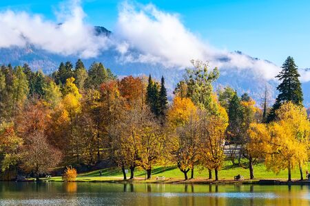 Photo pour Slovenia, lake Bled view with multi colored autumn trees and mountains with clouds - image libre de droit