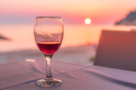 Photo for Romantic glass of wine. Sunset on beach reflected in red wine, summertime vacation concept - Royalty Free Image