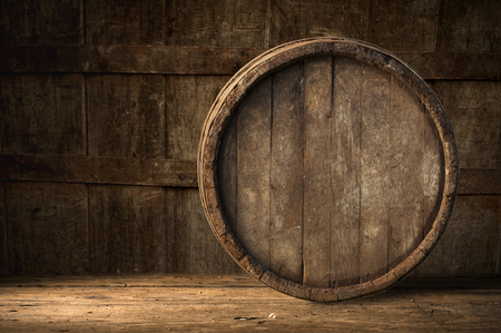 Beer barrel with beer glass on table on wooden background