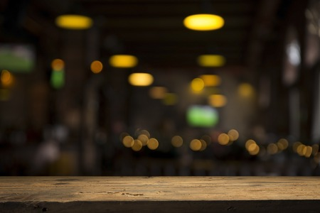 Photo pour image of wooden table in front of abstract blurred background of resturant lights - image libre de droit