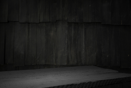 Photo pour Old wood table with blurred concrete block wall in dark room background. - image libre de droit