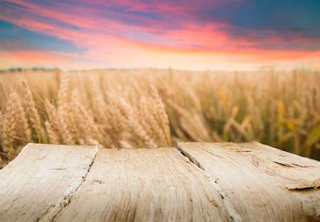 Photo pour Wood floor over yellow wheat field under nice sunset cloud sky background - image libre de droit