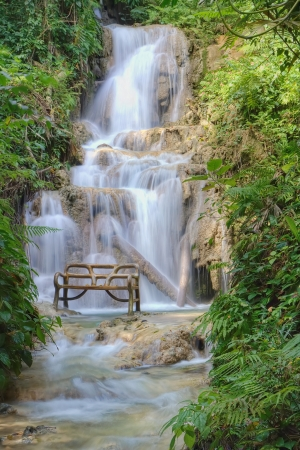 Waterfall and bench in a bea