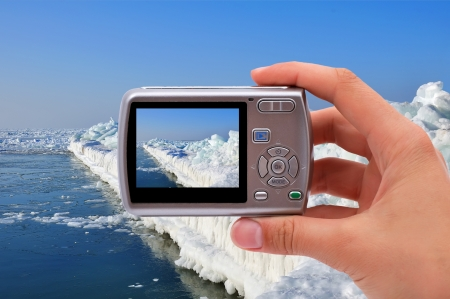 camera in hand of photographing ice pier
