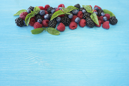 Various fresh summer berries on wooden background. Ripe raspberries, blackberries, blueberries and basil leaves. Berries at border of image with copy space for text.の写真素材