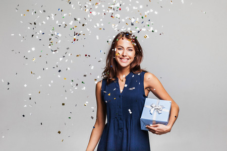 Photo for Beautiful happy woman with gift box at celebration party with confetti falling everywhere on her. Birthday or New Year eve celebrating concept - Royalty Free Image