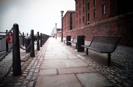 dark vignette of a bench on a footpath at liverpool docks